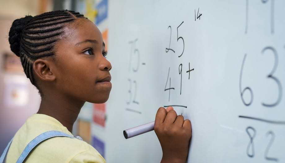 No longer struggling in math, the student is confidently writing her work on the board.