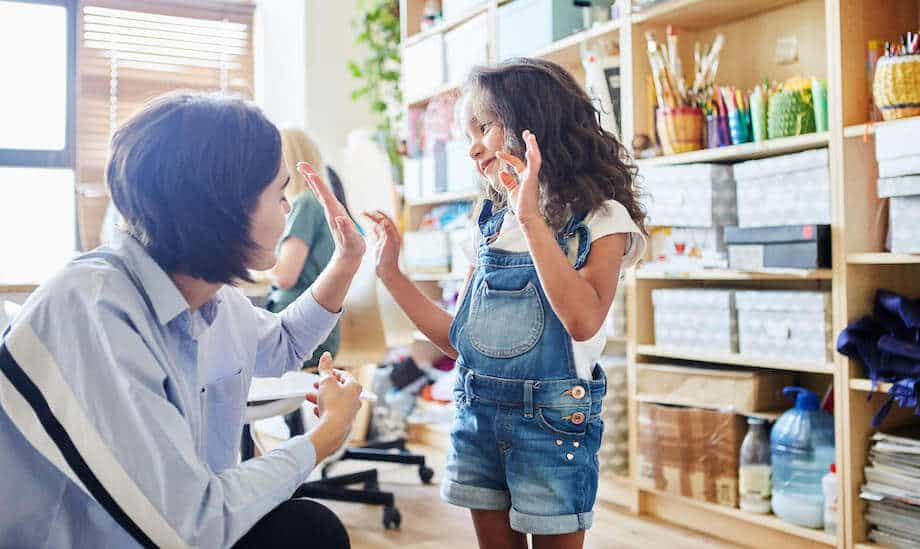 A teacher high-fiving a student, a simple example of positive reinforcement in the classroom